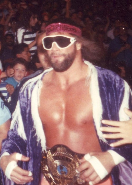 Professional wrestler Randy 'Macho Man' Savage, wearing the WWF Championship and running to the ring