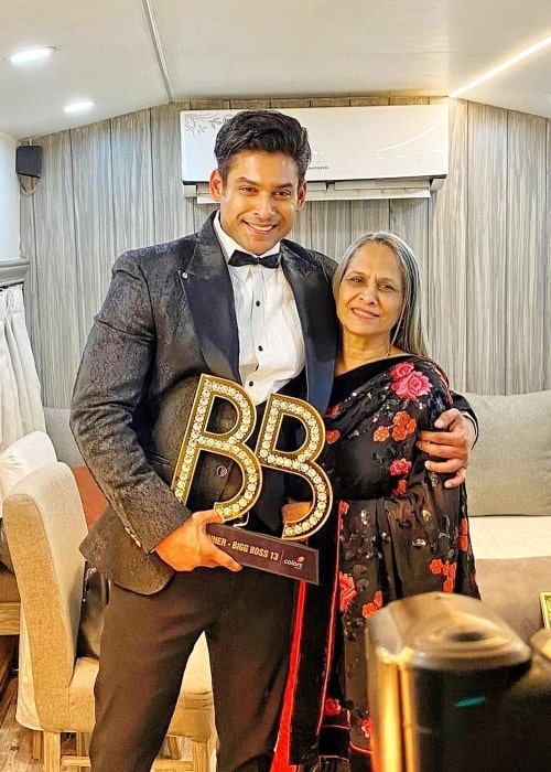 Sidharth Shukla holding his 'Big Boss' trophy and smiling in a picture alongside his mother in February 2020