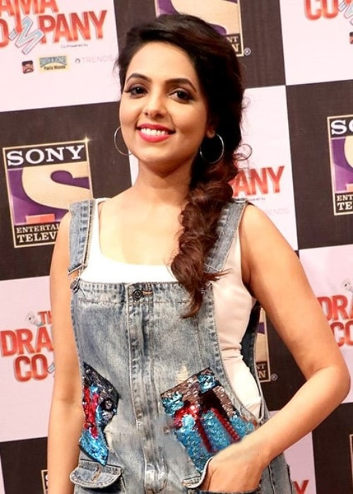 Sugandha Mishra smiling for the camera at the press conference of the show 'The Drama Company' in July 2017