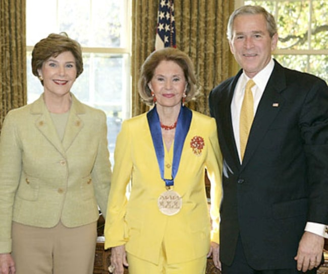 Cyd Charisse (Center) pictured with George W. and Laura Bush while accepting the National Medal of Arts and Humanities Award in an Oval Office ceremony on November 9, 2006