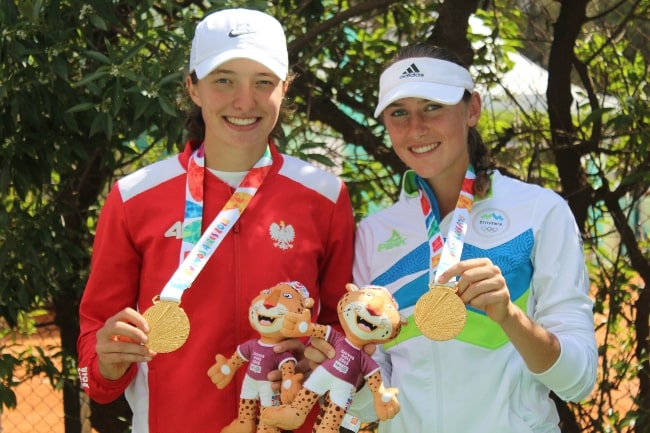 Iga Świątek (Left) and Kaja Juvan posing as the 2018 Summer Youth Olympics gold medallists in girls' doubles