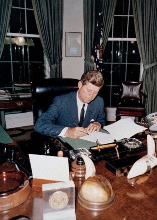John F. Kennedy pictured while signing the Proclamation for Interdiction of the Delivery of Offensive Weapons to Cuba at the Oval Office on October 23, 1962