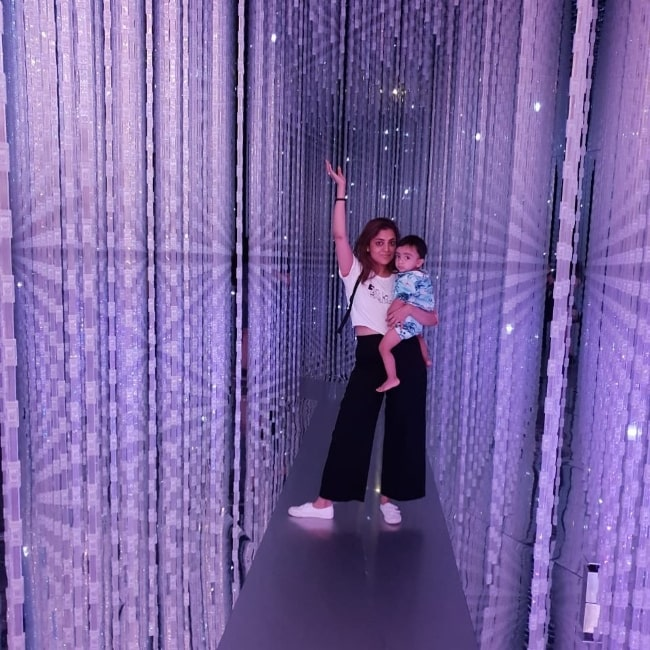 Nisha Agarwal posing for a picture while holding her son at ArtScience Museum in Singapore in June 2019
