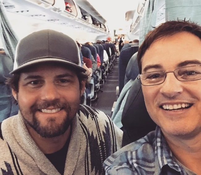 Kerr Smith (Right) smiling in a selfie alongside Kristoffer Polaha at Vancouver International Airport in March 2020