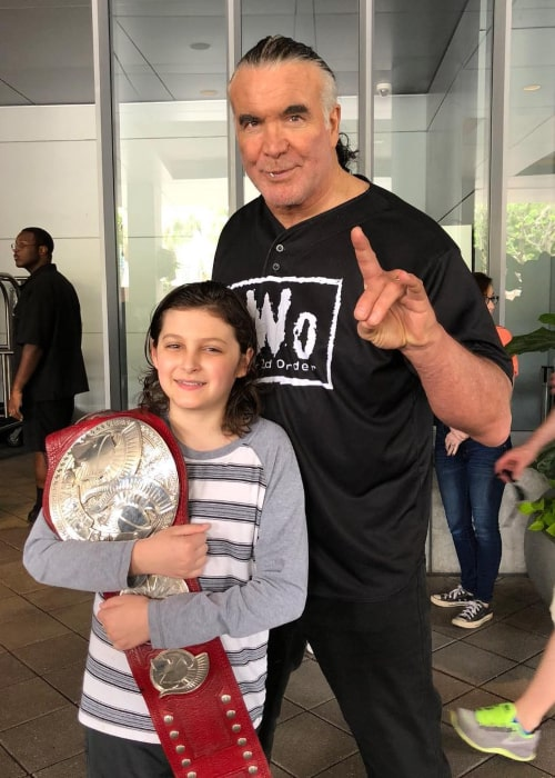 Scott Hall posing with a young fan in April 2018
