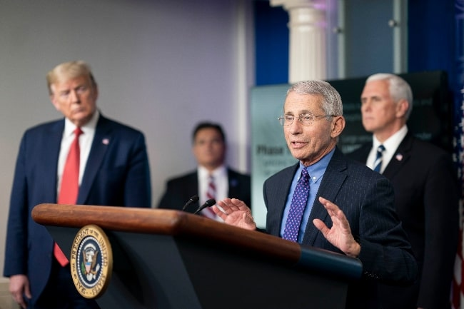 Anthony Fauci pictured while speaking to the White House press corps on COVID-19 in April 2020, watched by President Donald Trump (Left) and Vice President Mike Pence (Right)