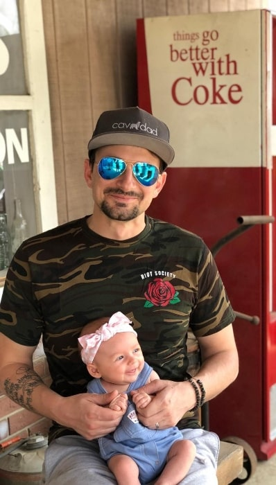 Evan Bass as seen while smiling for a picture with his baby at Country Living Fair in April 2018