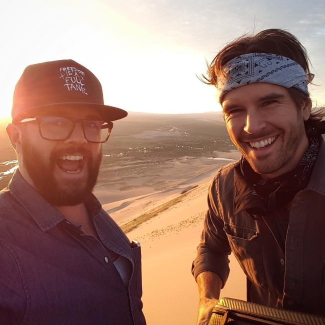 Graham Wardle (Right) smiling in a selfie alongside Peter Harvey at the top of the dunes in Mongolia