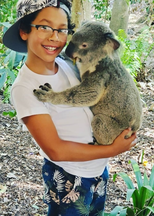 Adrian Groulx smiling for the camera while holding a koala