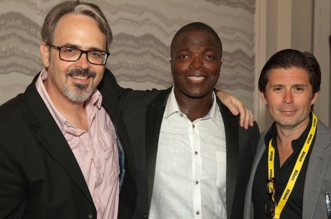 The producer of the movie titled 'The Week' posing for the camera alongside Reno Wilson (Center) and Rick Gomez (Right) in June 2015
