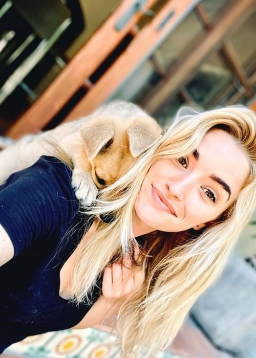 Brianne Howey smiling for a picture with her dog in May 2020