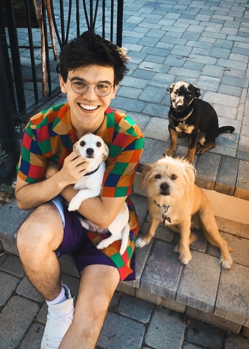 MacKenzie Bourg smiling for a picture with his furry friends in August 2019