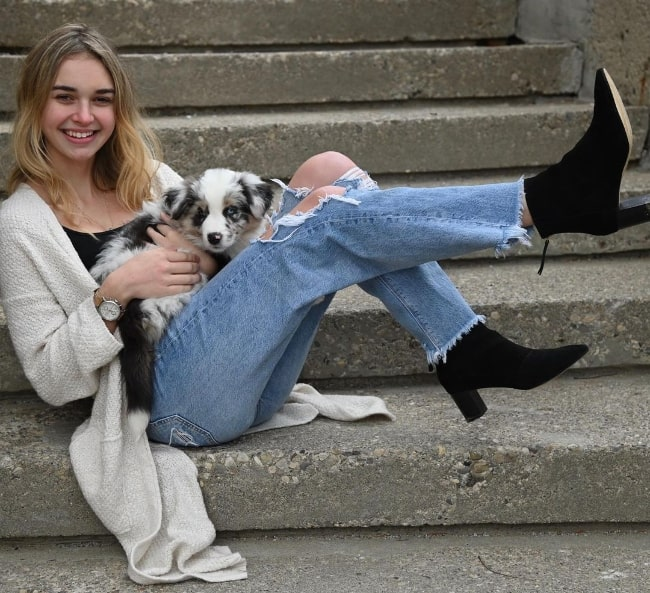 Nikki Roumel posing for a picture with her dog in December 2020