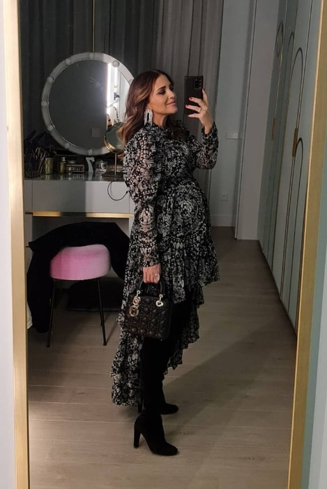 Paula Echevarría taking a mirror selfie while showing her baby bump in January 2021