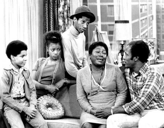 From Left to Right - Ralph Carter, BernNadette Stanis, Jimmie Walker, Esther Rolle, and John Amos as seen in a photo of the Evans family from the television program 'Good Times'