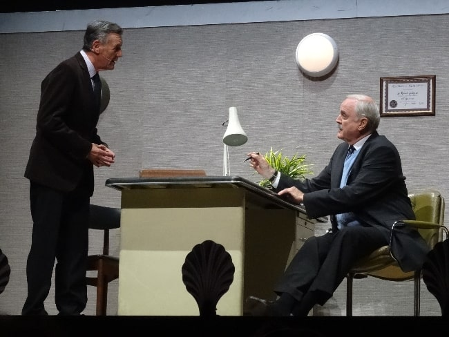 John Cleese and Michael Palin (Standing) during the 'Argument Clinic' sketch at 'Monty Python Live (Mostly)' in 2014