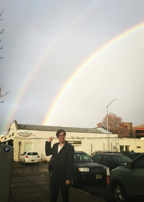 David W. Thompson posing for a picture with a backdrop of two rainbows at Peekskill Coffee in November 2016