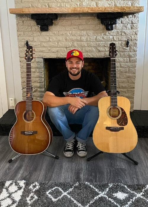 Chayce Beckham posing for a picture with 2 guitars in June 2021