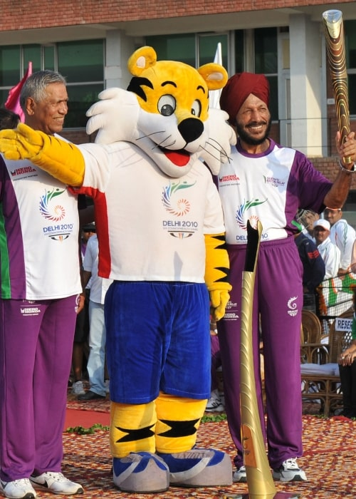 Milkha Singh holding the Queen's Baton 2010 Delhi with another athlete G S Virithi and Shera, the Mascot of Commonwealth Games 2010 Delhi, at the Cricket Stadium in Chandigarh on July 3, 2010