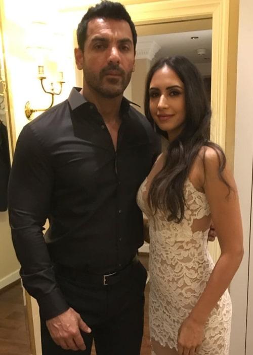 Priya Runchal posing for the camera alongside John Abraham in February 2019