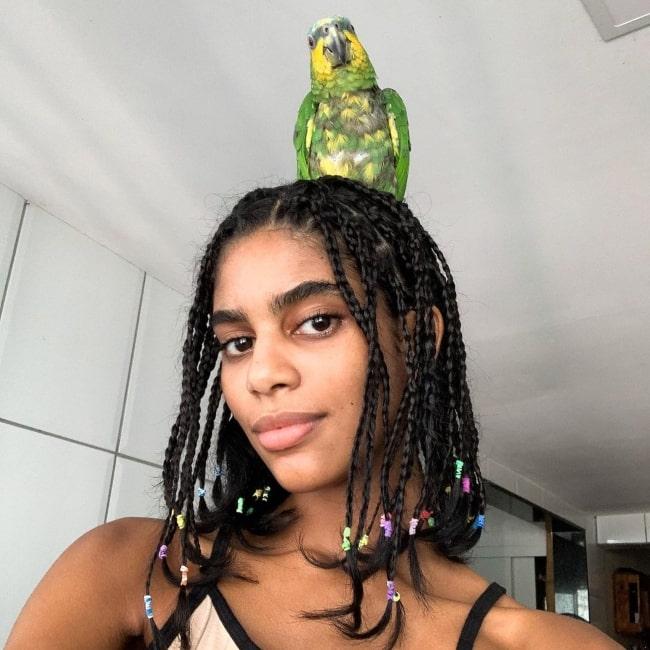 Allana Santos Brito as seen in a selfie with a parrot that was taken in Salvador, Bahia, Brasil in April 2020