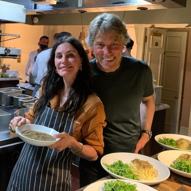 John Bishop smiling in a picture alongside Courteney Cox in 2021