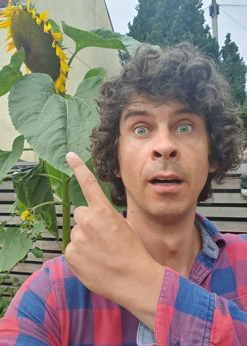 Andy Day as seen while taking a selfie with a sunflower in the background in July 2020