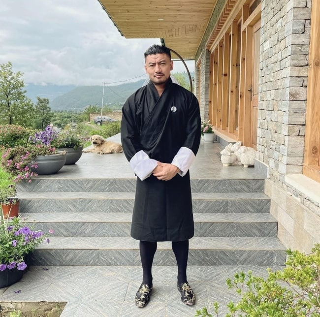 Sangay Tsheltrim posing for a picture in a traditional dress in Bhutan