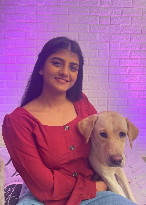 Gabriella Charlton smiling for a picture with her dog in 2021