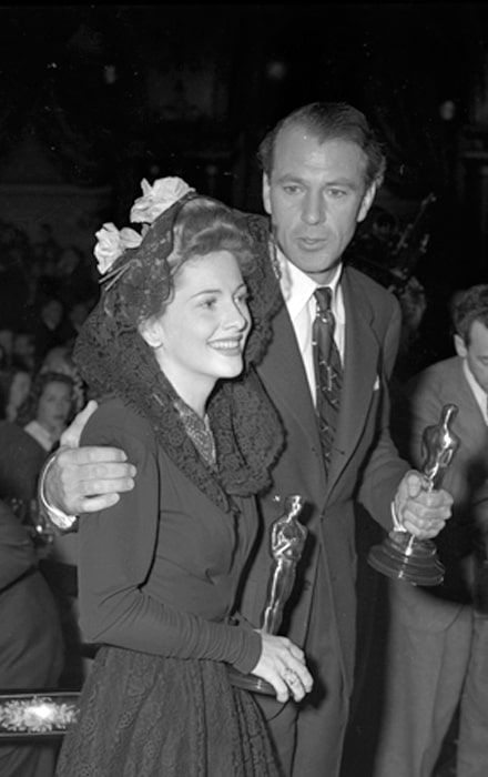 Gary Cooper and Joan Fontaine pictured while holding their Oscars at the Academy Awards after party, 1942