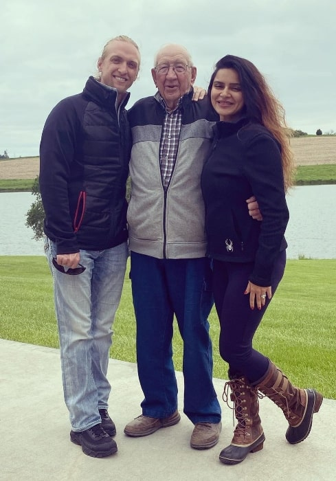 Aashka Goradia smiling for a picture with her husband and grandfather-in-law in Omaha, Nebraska
